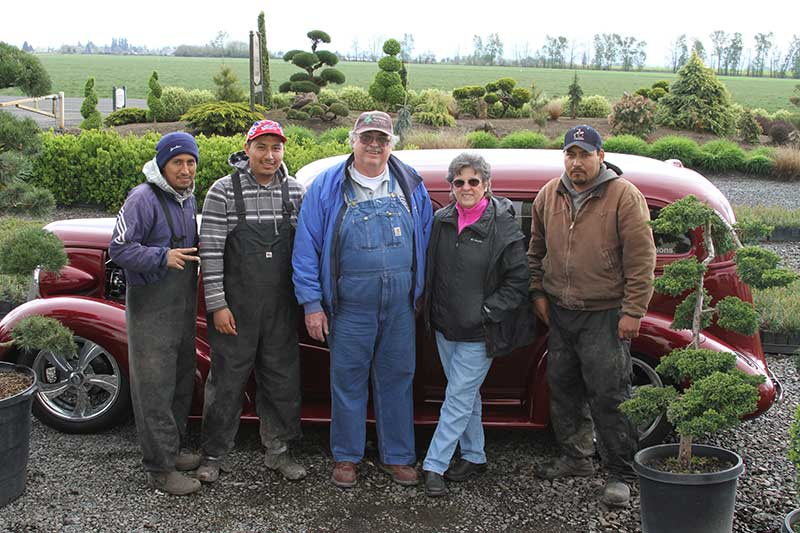 "McKinnon Nursery owners David ""Mac"" McKinnon (center) and Nancy McKinnon pose with employees (left to right) Mario Martinez, Alejandro Martinez and Refugio Nolasco. Also shown: Mac's 1937 Chevrolet Sedan Delivery, and an assortment of material grown at the nursery."