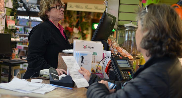 Brenda Powell rings up a transaction on her point-of-sale system for customer Miriam Edell at Garland Nursery in Corvallis. Photo by Denise Ruttan