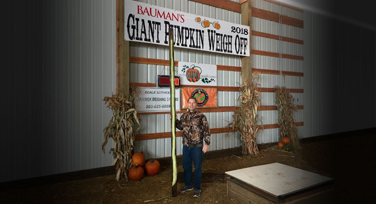 Brian Williams stands with a long gourd at a weigh off event at Bauman's Farms in Gervais, Oregon. Photo by Kristine Williams