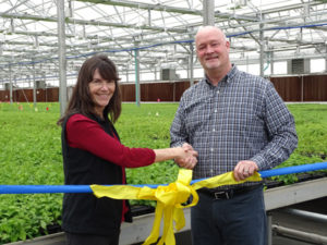 Agricultural Department manager Debbie Thorne and president Scott Crownover cut the ribbon on a new clean-stock greenhouse. Photo courtesy of Skagit Horticulture.